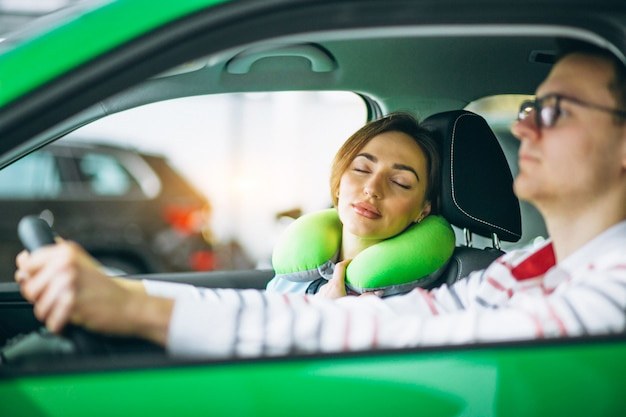 Woman sleeping in car on pillow and driving with her husband Free Photo