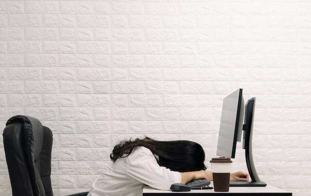 A woman sleeping on the desk computer screen Premium Photo