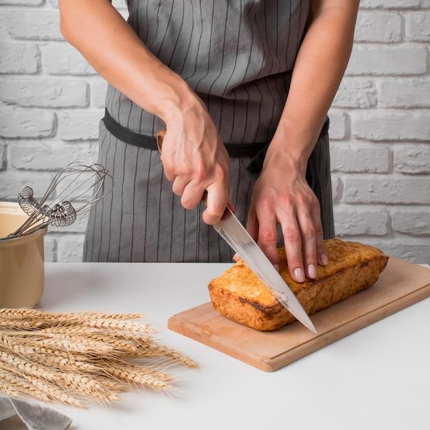 Donna che affetta il pane di banana Foto Gratuite