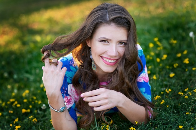 Woman smiles in a summer green glade with flowers. Premium Photo