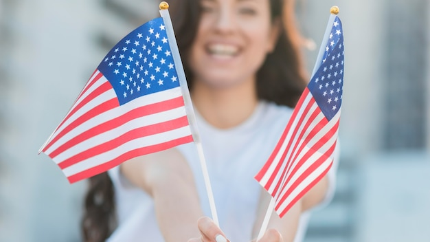 Женщина улыбается и держит флаги сша Бесплатные Фотографии