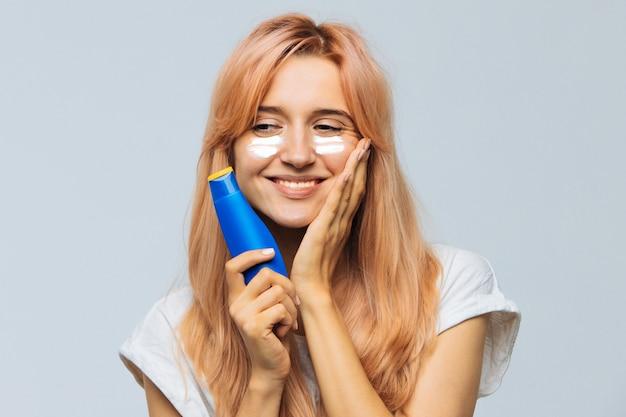 Woman smiling and applying suntan cream (sunscreen lotion) on face, cheeks with sun protection cream. sunburn Premium Photo