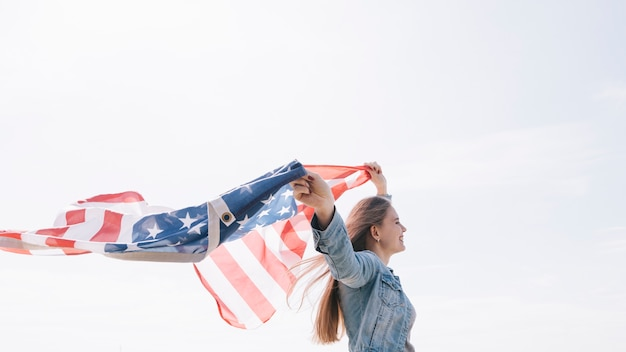 Woman smiling and holding wide waving  american flag high in sky Free Photo