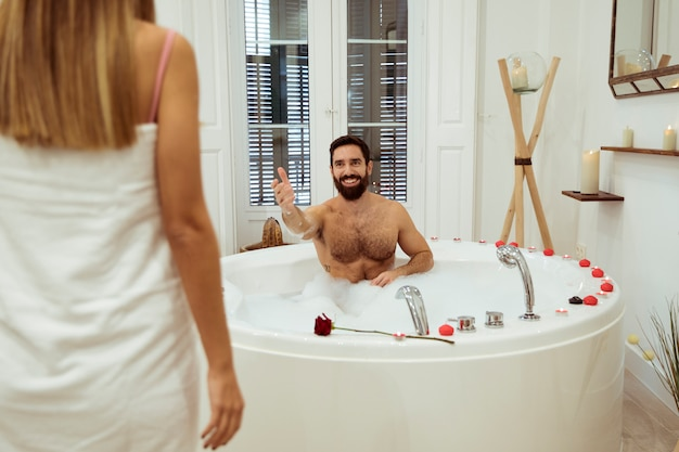 Woman and smiling man in spa tub with foam Free Photo