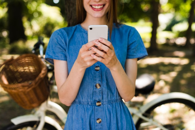Woman smiling at phone with defocused bike Free Photo
