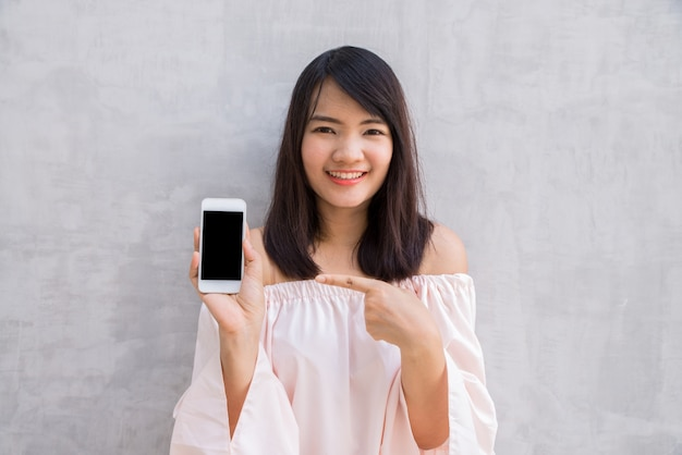 Woman smiling pointing at her cellphone Free Photo