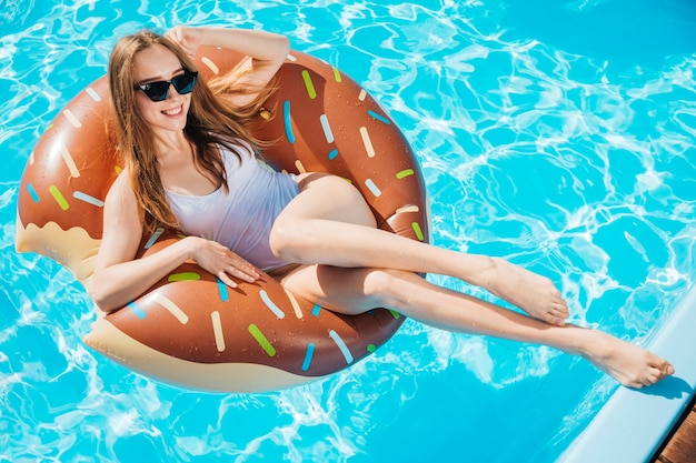 Woman smiling and posing on doughnut swim ring Free Photo