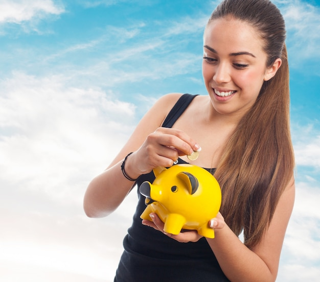 Woman smiling pouring a coin into a piggy bank Free Photo