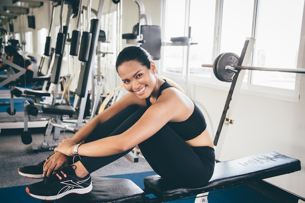 Woman smiling sitting on a weight machine Free Photo