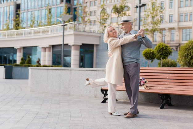 Woman smiling. two pensioners dance in park. Premium Photo