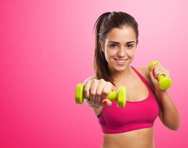 Woman smiling while giving a punch with dumbbells in hands Free Photo