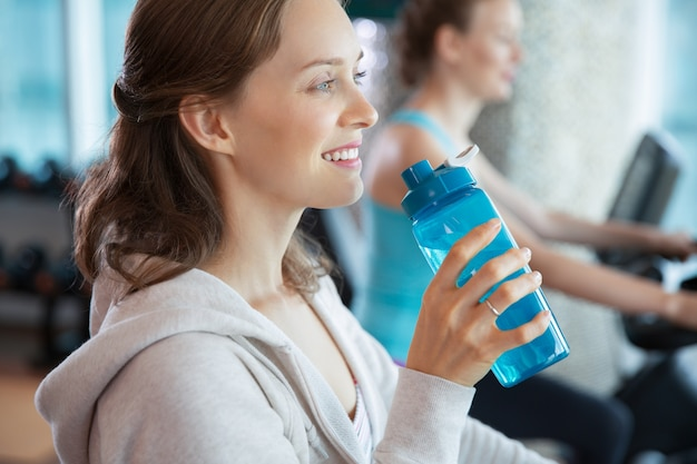 Woman smiling with a bottle of water Free Photo
