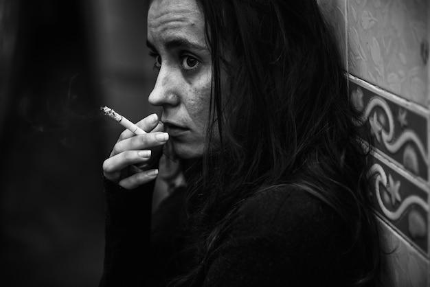 Woman smoking cigarette alone grayscale Free Photo