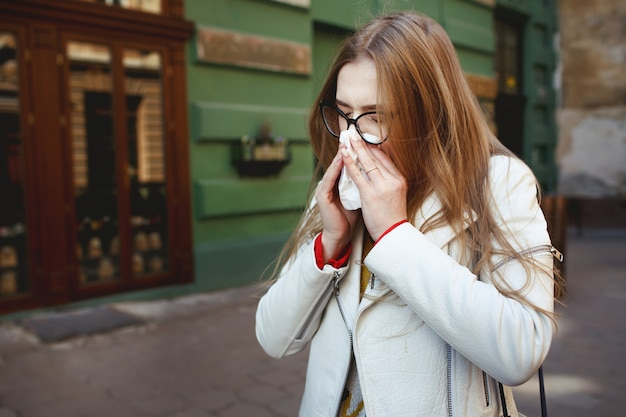 Woman sneezes standing on the street  Free Photo