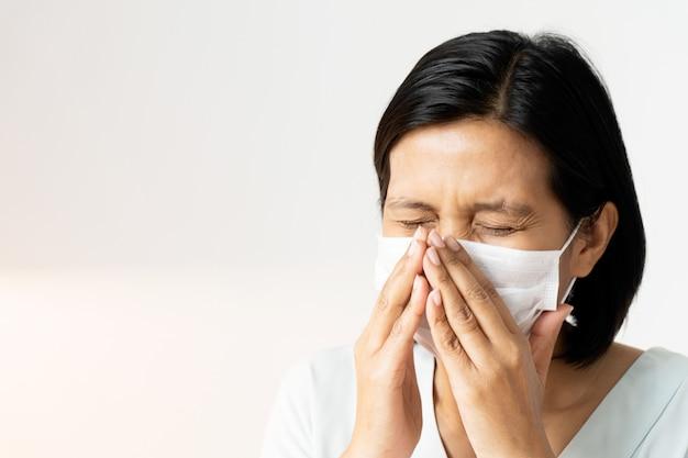 Женщина чихает под маской, прикрывая рот и нос во время кашля. корона вирус или концепция covid-19. Premium Фотографии