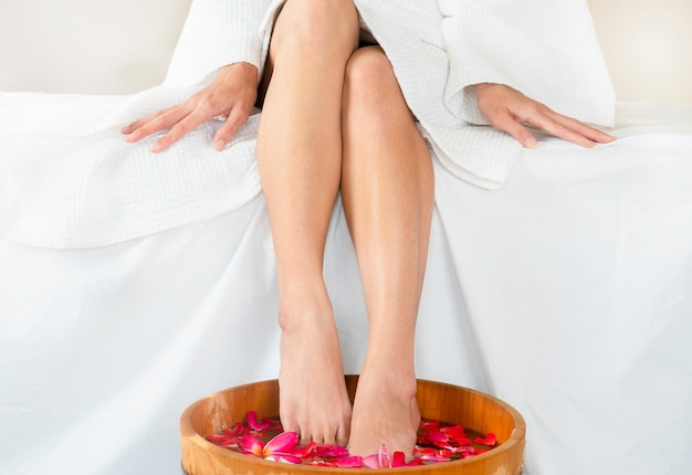 Woman soaking feet in wooden spa bowl of water with floating flowers at spa. Premium Photo