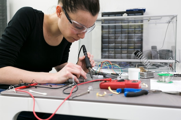 Woman soldering pieces at table