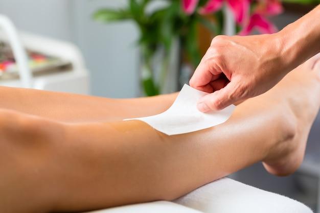 Woman in spa getting leg waxed Premium Photo
