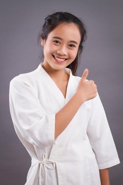Терапевт спа женщины указывая большой палец вверх. азиатская женщина спа-терапевт Premium Фотографии