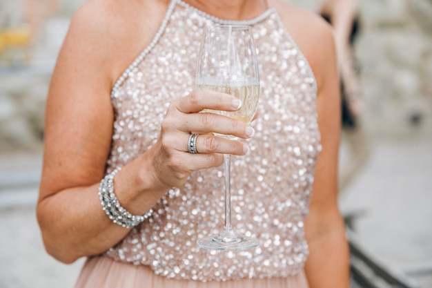 Woman in sparkling pink dress holds glass of champagne in her ar Free Photo