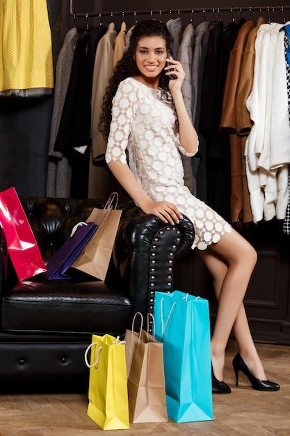 買い物でショッピングモールに座っている女性が電話で話す 無料写真