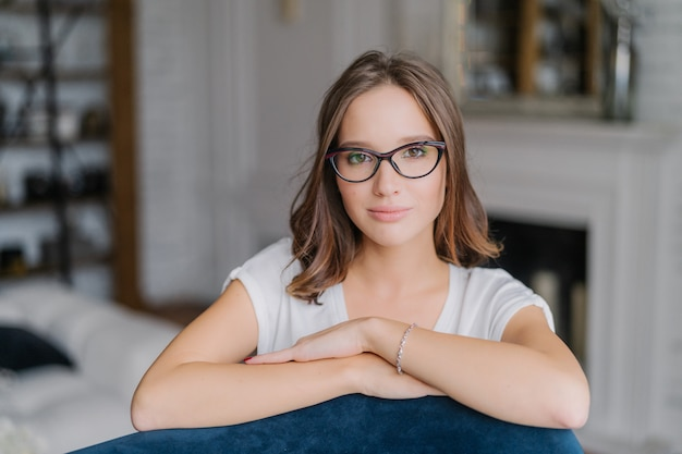 Woman in spectacles, keeps hands on back of sofa, poses in living room at home. Premium Photo