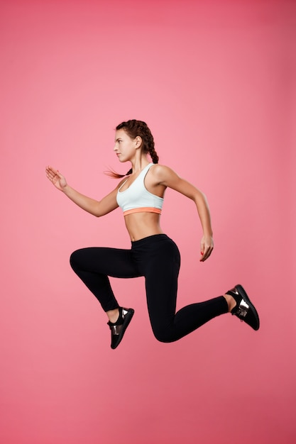 Woman in sport clothing pretends running in air jumping high Free Photo