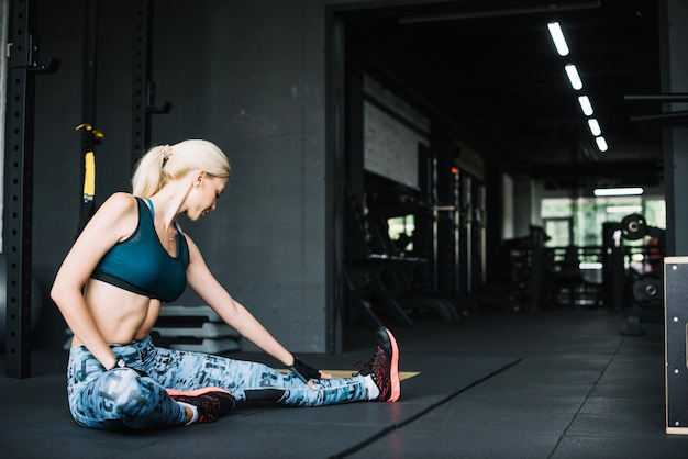 Woman in sports bra and leggings stretching Free Photo