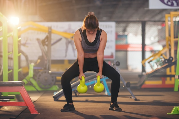 Woman in sportswear doing crossfit workout with kettle bell. healthy concept Premium Photo