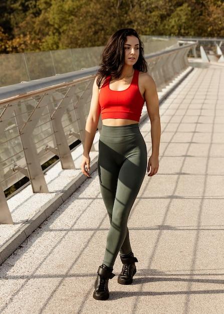 Donna in abiti sportivi in posa all'aperto Foto Gratuite