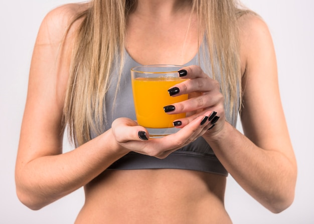 Woman in sportswear with glass of juice Free Photo