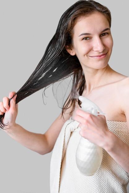 Женщина распыляет волосы с продуктом Бесплатные Фотографии