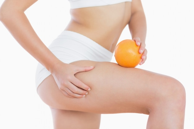 Woman squeezes cellulite skin on thigh as she holds orange Premium Photo