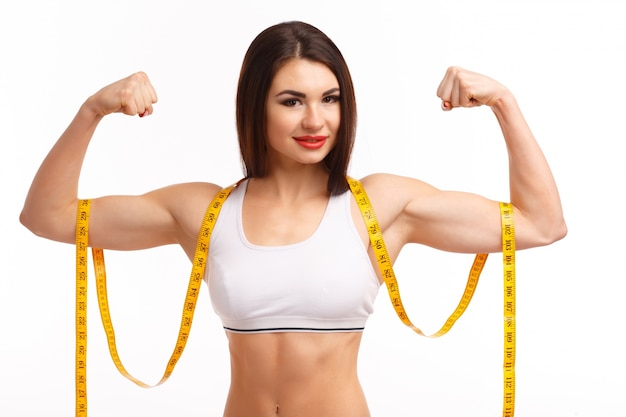 Woman squeezing both biceps and a tape measure Free Photo