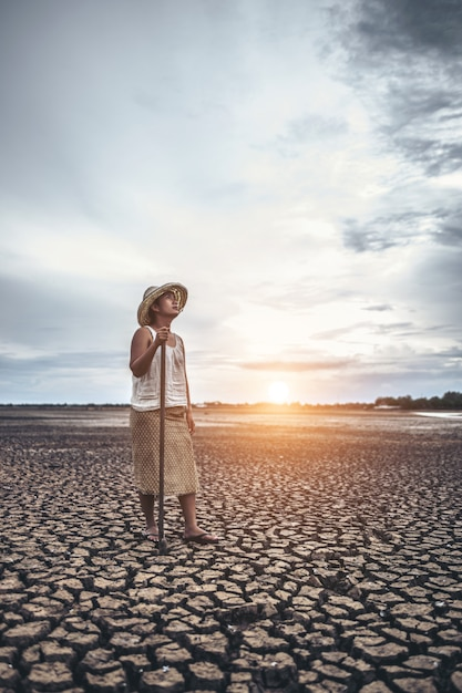 The woman stand his hand and caught a siem on dry soil and looked at the sky. Free Photo
