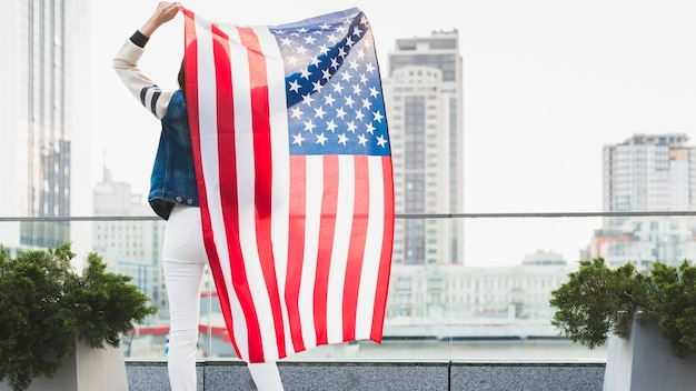 Woman standing on balcony with big american flag Free Photo