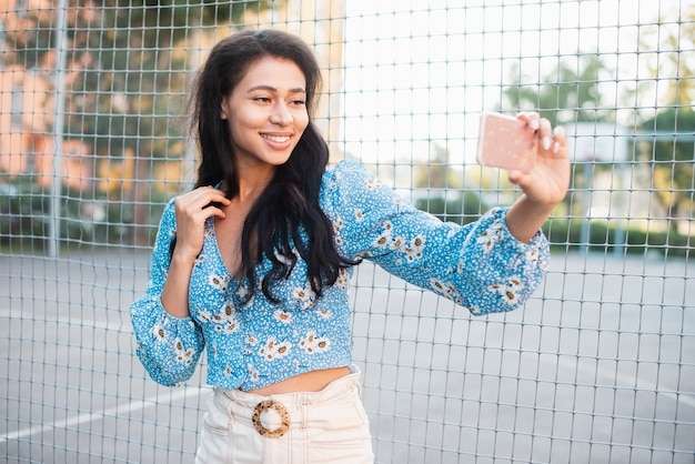 Woman standing next to a basketball field taking a self photo Free Photo