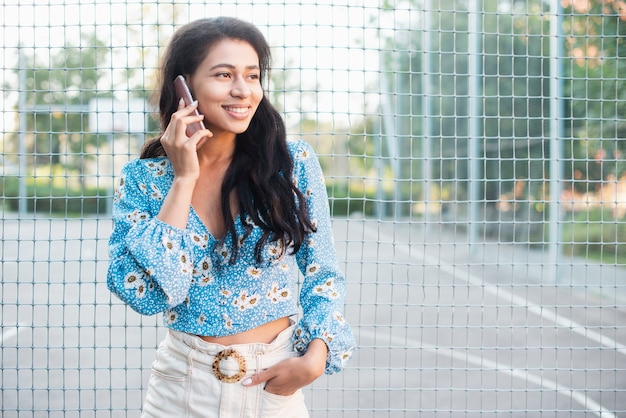 Woman standing next to a basketball field talking at the phone Free Photo