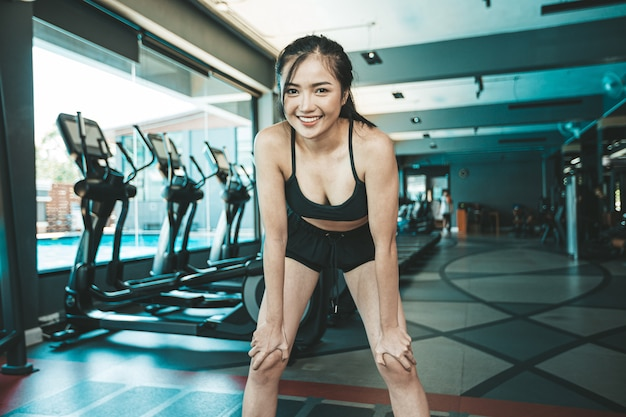 Woman standing bent over and hand catch knees before exercise in the gym. Free Photo