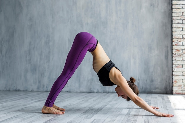 Woman standing in a downward-facing dog yoga pose Free Photo
