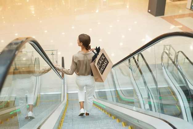 Woman standing on escalator Premium Photo