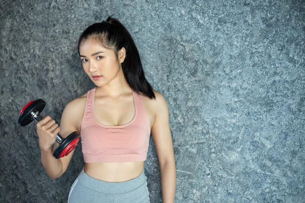 Woman standing exercising with a red dumbbell in the gym. Free Photo