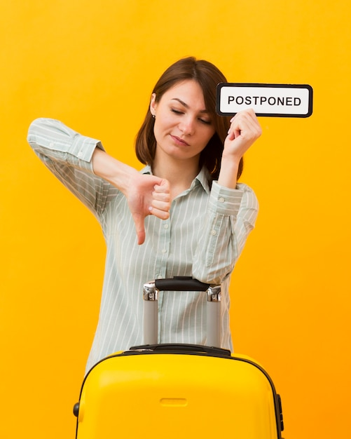 Woman standing next to her luggage while holding a postponed sign Free Photo