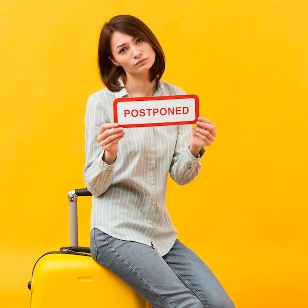 Woman standing on her luggage while holding a postponed sign Free Photo