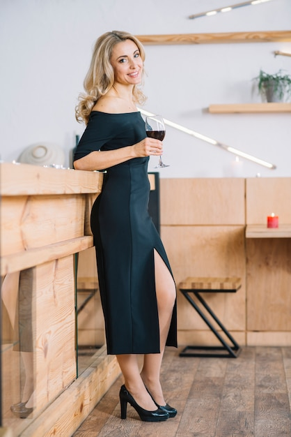 Woman standing and holding wine glass Free Photo