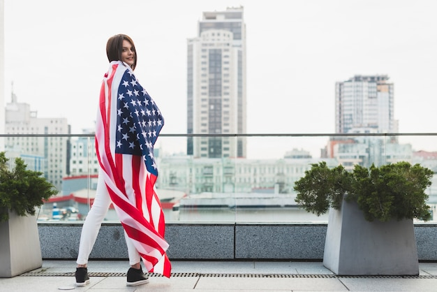 大きなアメリカ国旗と半回転で立っている女性 無料写真