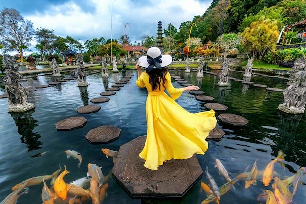 Женщина, стоящая в пруду с разноцветными рыбками в водном дворце тирта гангга на бали, индонезия Бесплатные Фотографии