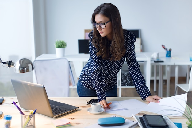 Woman standing looking at her laptop computer Premium Photo