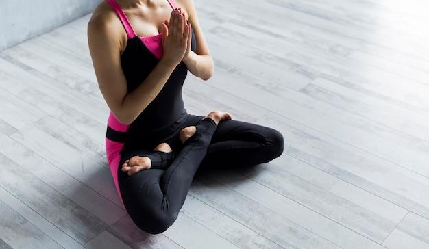 Donna che sta nella posa di yoga del loto con le mani contro il suo petto Foto Gratuite