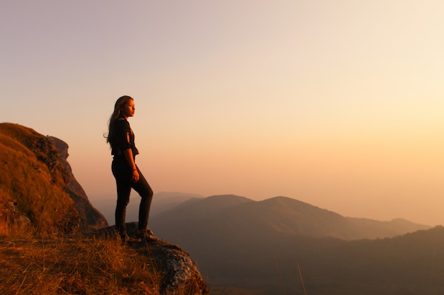 Woman standing on a mountain looking at sunset Free Photo